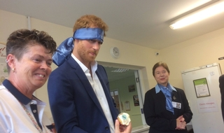 Prince Harry being shown the work of the Headway charity