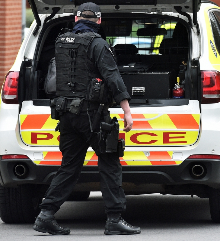 Police activity: A firearms officer outside the flats in Lee Bank, Birmingham