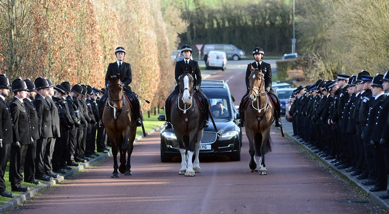Guard of honour: Colleagues bow their heads as the funeral cortege of PC Kevin Flint passes on its way to Amersham crematorium