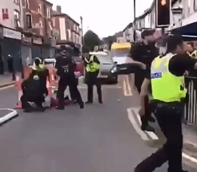 Man detained: Officers hold a suspect in Moseley after an officer was run over by his own police vehicle    Image from @imjustbrum instagram video
