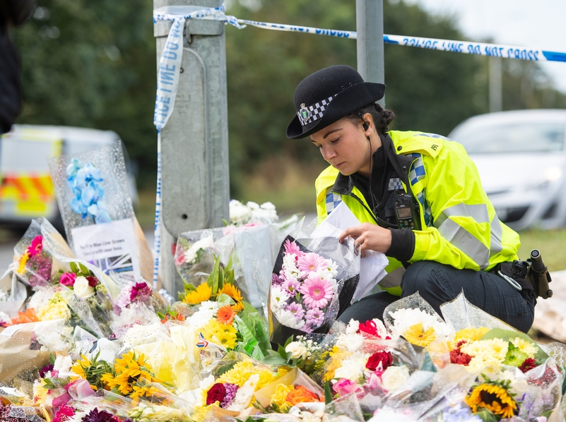 Floral tributes: An officer looks at the many messages left at the scene where PC Andrew Harper was killed