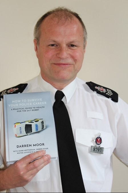 Kent Sgt Darren Moor with a copy of his book