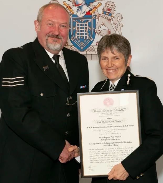 Sergeant Paul Newman receives his bravery award from the Met Commissioner for saving the life of an HGV driver.