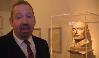 Alfie Moore next to a death mask at the exhibit