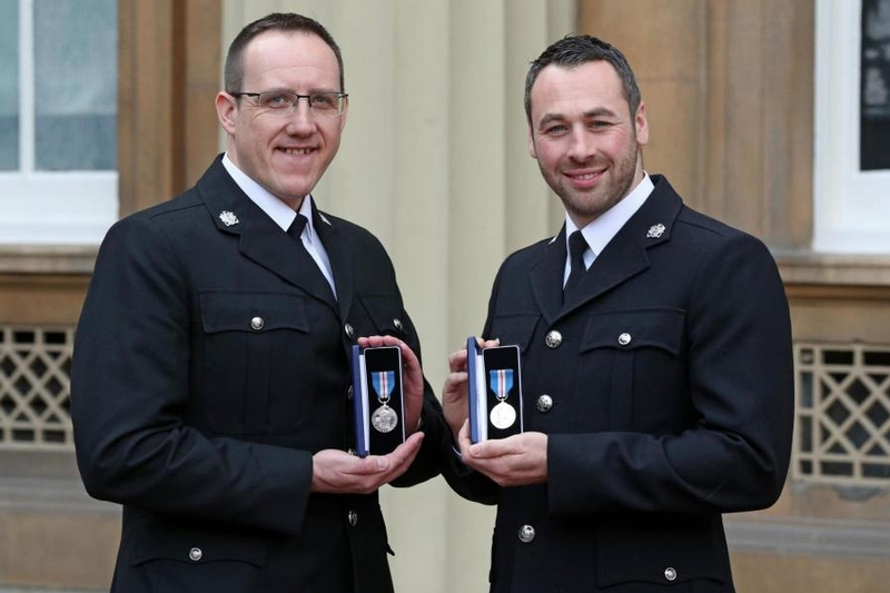 West Yorkshire Police Constables Craig Nicholls, left, and Jonathan Wright, right, after they were honoured by the Queen PA